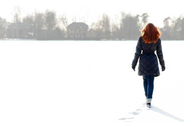 Pretty girl walking on frozen lake